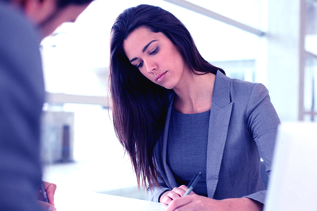 Businesswoman writing on document after meeting
