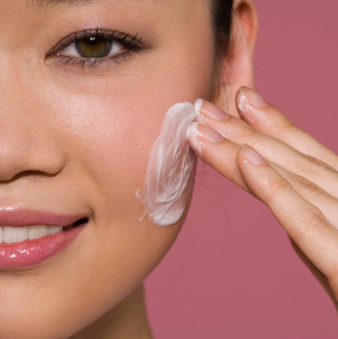 Woman applying facial moisturizer